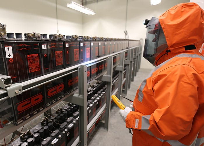 Worker wearing orange PPE looking at batteries on racks
